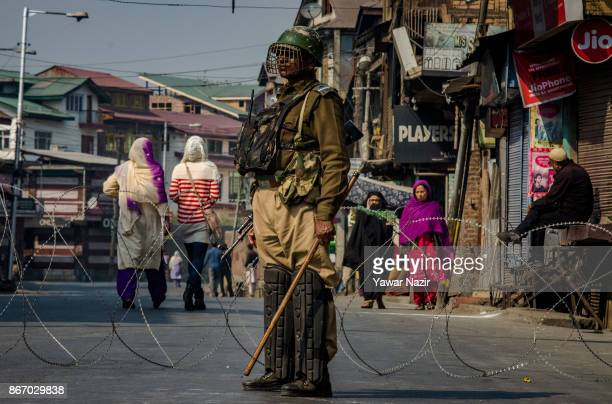 An Indian paramilitary trooper stands alert as Kashmiri Muslims women walk on a deserted road during a strike on October 27 2017 in Srinagar the...