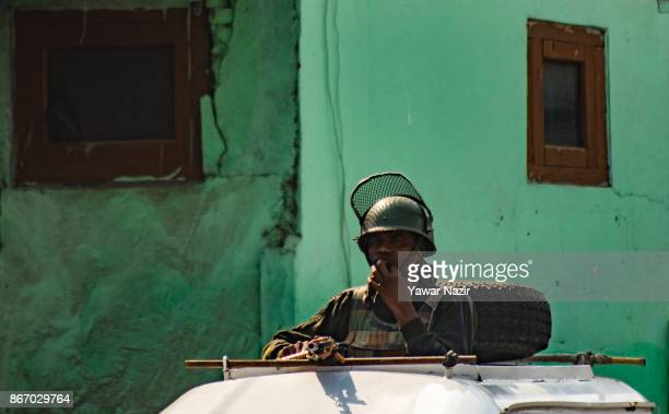 An Indian paramilitary trooper stands alert atop his armored vehicle during a strike on October 27 2017 in Srinagar the summer capital of Indian...