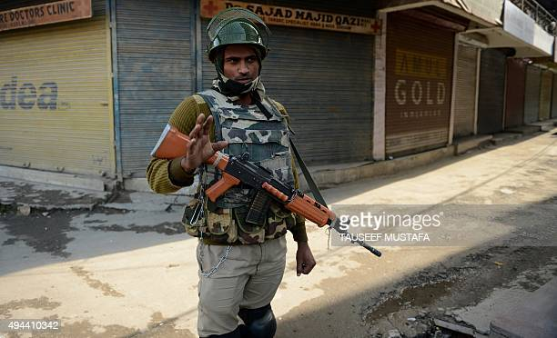 An Indian paramilitary trooper stands alert during a one day strike in Srinagar on October 27 which commemerates the arrival of the Indian Army in...