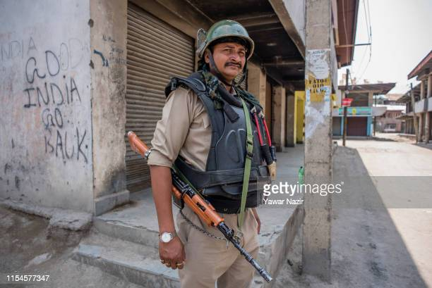 An Indian paramilitary trooper stands alert in front the shuttered shops during a strike restrictions on the third death anniversary of Burhan Wani...