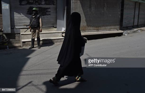 TOPSHOT An Indian paramilitary trooper stands guard as a Kashmiri woman walks near the Jamia Masjid mosque in Srinagar on September 15 2017 The...