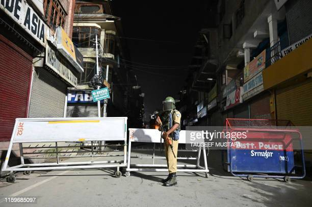 TOPSHOT An Indian paramilitary trooper stands guard at a roadblock at Maisuma locality in Srinagar on August 4 2019 Fears of an impending curfew in...