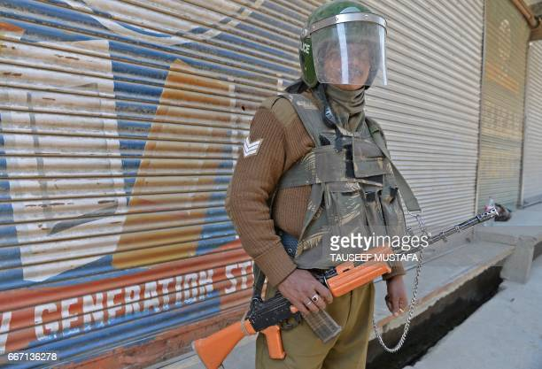 An Indian paramilitary trooper stands guard during a strike after eight people were killed in Srinagar on April 11, 2017. Eight civilians were killed...