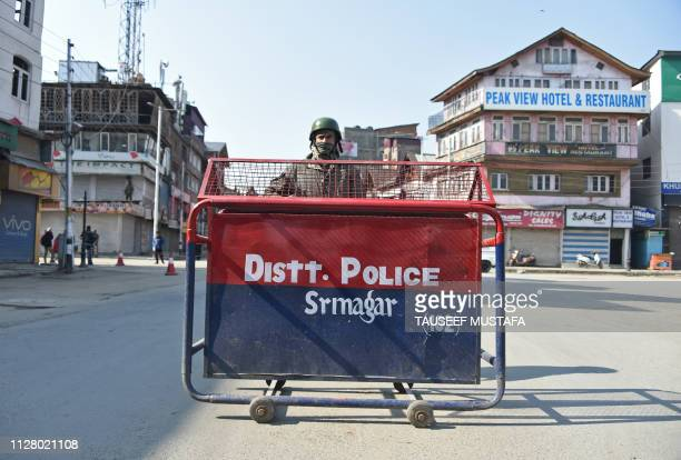An Indian paramilitary trooper stands guard during the second day of strike called by separatists against the National Investigation Agency raids at...