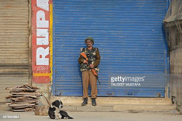 An Indian paramilitary trooper stands guard in front of a shuttered shop during a oneday strike called by Kashmiri separatists protesting against...