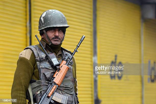 An Indian Paramilitary trooper stands guard in front of closed shops during a strike held on World Human Rights Day in Srinagar on December 10, 2012....