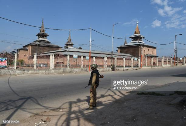 An Indian paramilitary trooper stands guard in front of the Jamia Masjid mosque during a curfew in Srinagar on July 8 2017 India on July 8 imposed a...