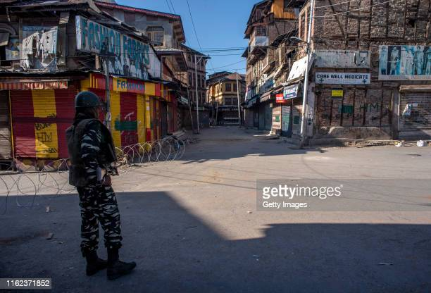 An Indian paramilitary trooper stands guard near a razor wire cordon amid curfew like restrictions in the Habba Kadal on August 18 2019 in Srinagar...
