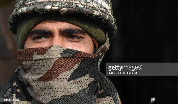 An Indian paramilitary trooper stands guard near Jamia Masjid mosque during a restriction in Srinagar on December 8 2017 A partial restrictions have...