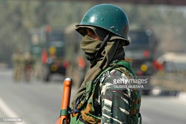 An Indian paramilitary trooper stands guard near the site of an attack by suspected militants on Pampore national highway on the outskirts of...