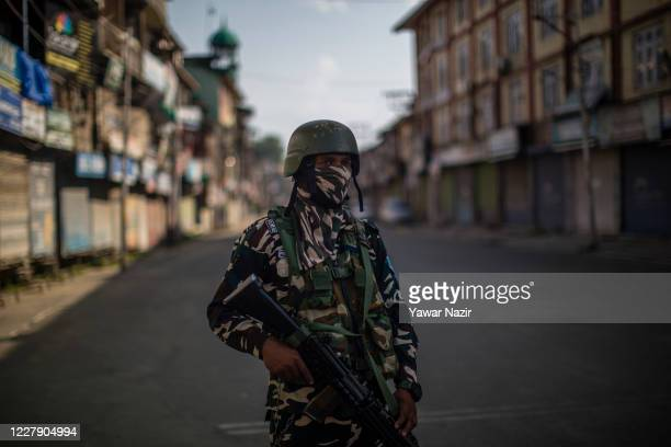 An Indian paramilitary trooper stands guard on a deserted road in the city center's commercial hub, during a curfew on August 04, 2020 in Srinagar,...