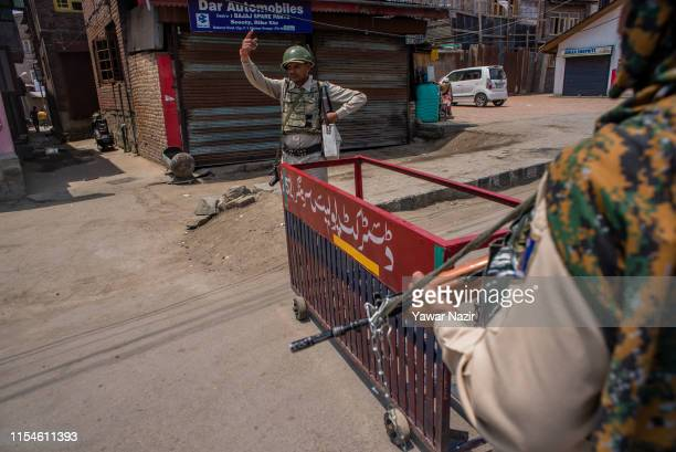An Indian paramilitary trooper stands guard on a road during a shutdown on the third anniversary of the death of Burhan Wani a popular commander of...