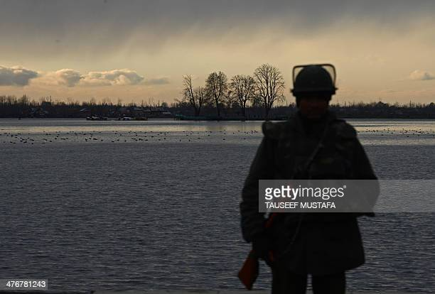 An Indian Paramilitary trooper stands guard on the banks of Dal lake in Srinagar on March 5,2014. India, the world's largest democracy, announced...