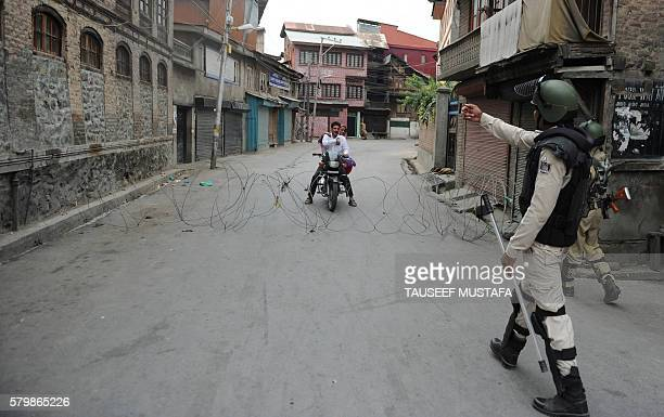 An Indian paramilitary trooper stops a Kashmiri couple on a motorbike during a seventeenth day of curfew in Srinagar on July 25 2016...