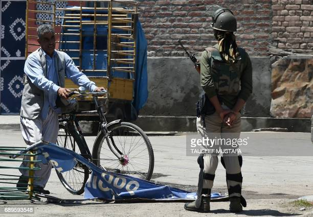 An Indian paramilitary trooper stops a Kashmiri man during a curfew in downtown Srinagar on May 29, 2017. Authorities imposed a curfew in many parts...