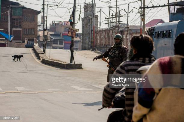 An Indian paramilitary trooper stops a Kashmiri scooterist on a deserted road in front Kashmir's Jamia Masjid in the Old City during restrictions on...