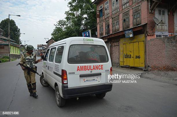 An Indian paramilitary trooper stops an ambulance during a curfew in Srinagar on July 12 2016 Thirty protesters were killed and over 300 injured in...
