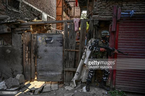 An Indian paramilitary trooper takes position to secure the area near the site of a grenade blast that was reported in Barbarshah area of Srinagar on...