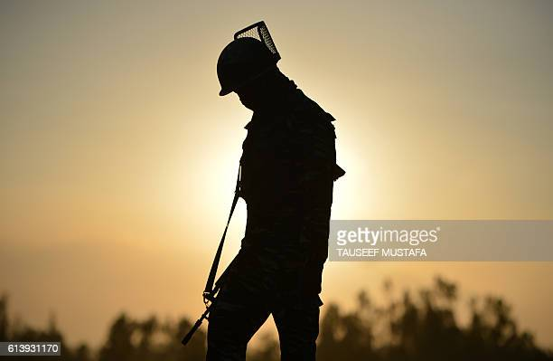 An Indian paramilitary trooper walks during the sunset near a building where suspested militants are thought to be hiding on the second day of a...