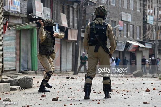 An Indian paramilitary trooper whirls a sling to launch a stone as Kashmiri demonstrators clash with Indian police during a demonstration against...