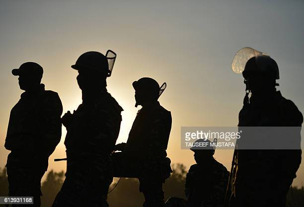 TOPSHOT An Indian paramilitary troopers look on during the sunset near a building where suspected militants are thought to be hiding on the second...