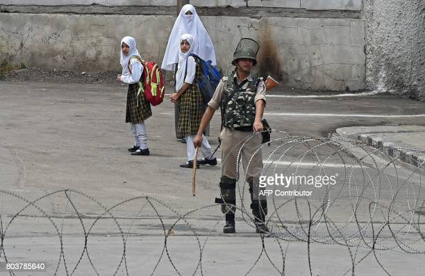 An Indian paramilitary troopers pulls a barbed wire fence across a road as Kashmiri students walk past in downtown Srinagar on June 30 2017 Indian...