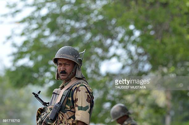 An Indian paramilitary troopers stands guard during a curfew in Srinagar on August 18 2016 More than 60 civilians have been killed in clashes between...