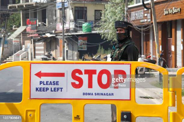An Indian paramillitary trooper stands alert besides a road block during strict restrictions in Srinagar Indian Administered Kashmir on 04 August...