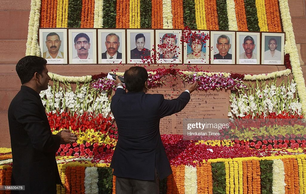 An Indian parliament officer pays floral tribute to colleagues who lost their lives in the 2001 attack on India's parliament during an event to mark the 11th anniversary of the attack, on December 13, 2012 in New Delhi, India. 14 persons lost their lives in a terrorist attack on Parliament in 2001.