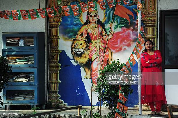 An Indian party worker for the Bharatiya Janata Party stands in front of an image of a Hindu goddess of Power Sheranwali Mata at the party's...