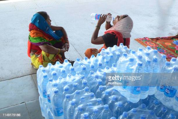 An Indian passenger drinks water near packed water bottles for sale in trains during a hot day at Allahabad Railway station on June 11 2019 Over half...