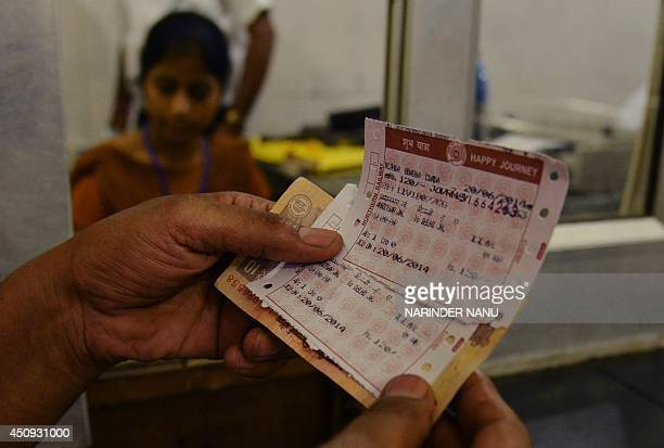 An Indian passenger poses for a photograph after buying train tickets at a railway station in Amritsar on June 20 2014 Railway passenger fares...