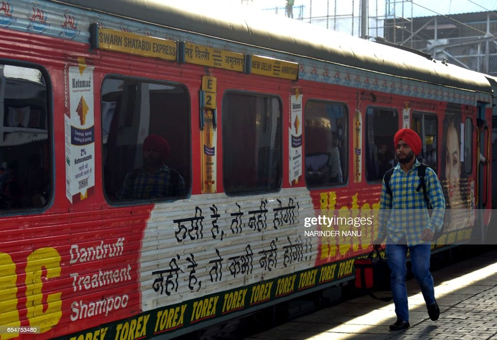 An Indian passenger walks past carriages of The Swarn Shatabdi Express at the railway station in Amritsar on March 18 2017 An Indian farmer`s battle..