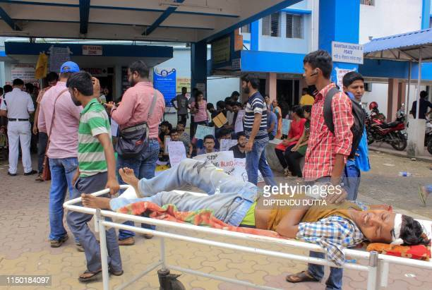An Indian patient is seen lying on a stretcher as in the background junior doctors hold placards during a protest at North Medical College and...