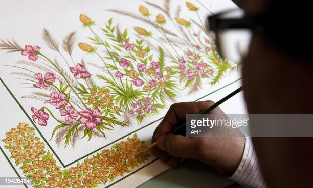 An Indian pattern designer paints a future fabric print at the April Cornell clothing factory in Noida on the outskirts of New Delhi on October 16...