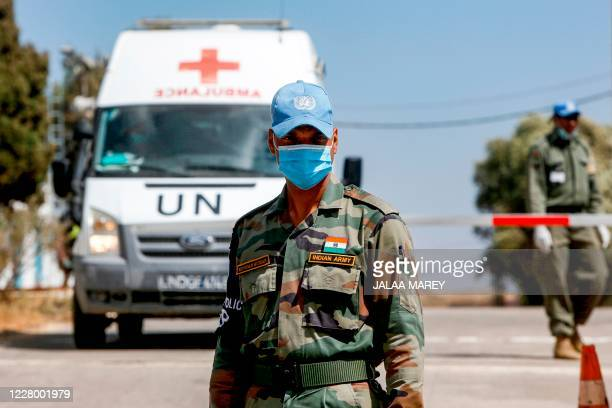 An Indian peacekeeper of the United Nations Disengagement Observer Force stands near ambulance transporting Wafaa Nasrallah, daughter of the last...