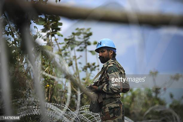 An Indian peacekeeper stands guard at a United Nations mobile operating base set-up during the past few days on the outskirts of Bunagana, in the...