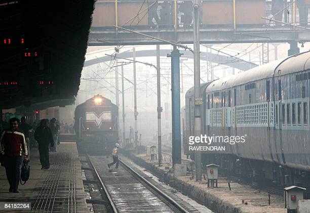 An Indian pedestrian crosses a railway track in dense fog at a station in New Delhi on January 1 2009 Heavy fog and cold across northern India has...