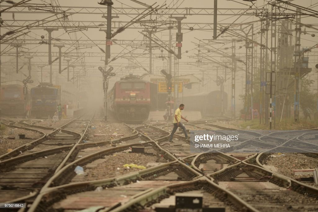 An Indian pedestrian crosses railway tracks as dust covers sky in Jalandhar on June 15 2018 Air pollution soared in New Delhi on June 14 to hazardous.