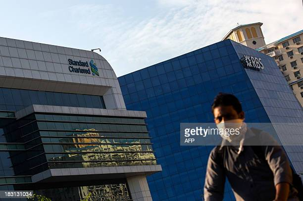 An Indian pedestrian cycles past the RBS and Standard Chartered banks in Gurgaon on the outskirts of New Delhi on October 5 2013 India's cabinet in...