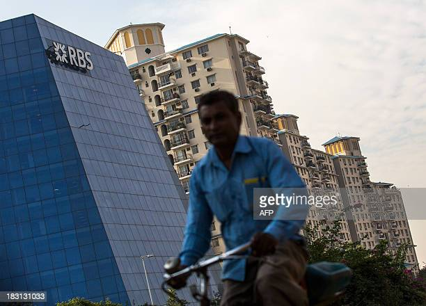 An Indian pedestrian cycles past the RBS bank and apartment blocks in Gurgaon on the outskirts of New Delhi on October 5 2013 India's cabinet in...