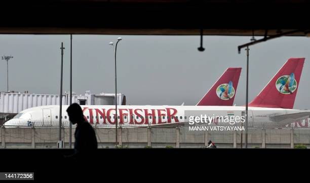 An Indian pedestrian is silhouetted as Kingfisher airlines planes are seen parked on the tarmac at the Indira Gandhi International Airport in New...