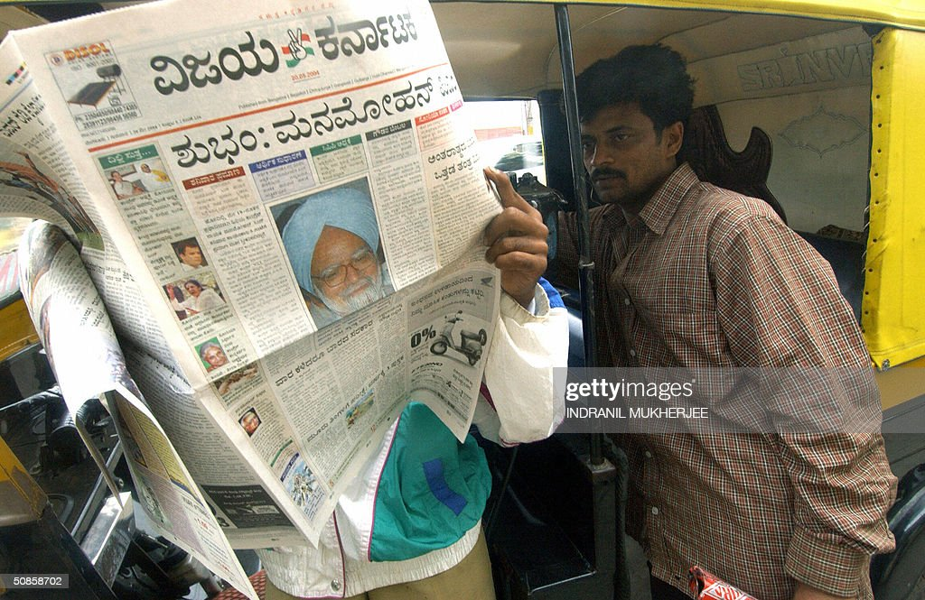 An Indian pedestrian (R) looks over the shoulder of an autorickshaw driver as he reads a morning newspaper with news of Manmohan Singh set to become India's next prime minister on its front page in Bangalore, 20 May 2004. Manmohan Singh, the father of India's economic reforms, was designated prime minister 19 May, after Italian-born Sonia Gandhi rejected emotional appeals to take the job. Singh, a 71-year-old Sikh who will be India's first non-Hindu prime minister, immediately pledged to turn the world's largest democracy into an economic model that 'makes new opportunities available to the poor.' AFP PHOTO/Indranil MUKHERJEE