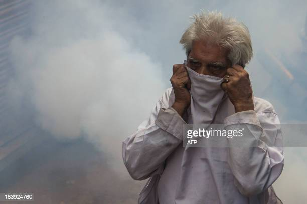 An Indian pedestrian protects his face as he is engulfed in a cloud of pesticide during a dengue prevention spraying in the Old Quarters in New Delhi...