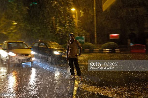 An Indian pedestrian stands in the middle of a street as heavy rain falls in New Delhi on July 17 2014 Rain fell in several areas of northern India...