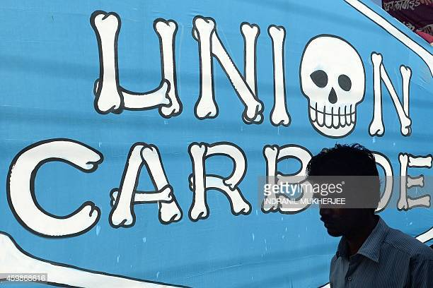 An Indian pedestrian walks past a poster bearing the name of the Union carbide company during a march by Bhopal Gas disaster victims to commemorate...