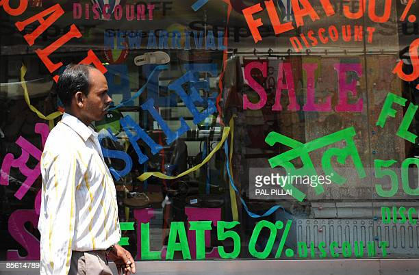 An Indian pedestrian walks past a shop window advertising discounted goods in Mumbai on March 26, 2009. Inflation in India edged closer to zero,...