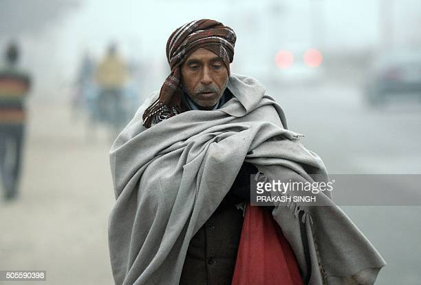 An Indian pedestrian wrapped in a blanket walks to work on a cold foggy morning in New Delhi on January 19 2016 AFP PHOTO / PRAKASH SINGH / AFP /...
