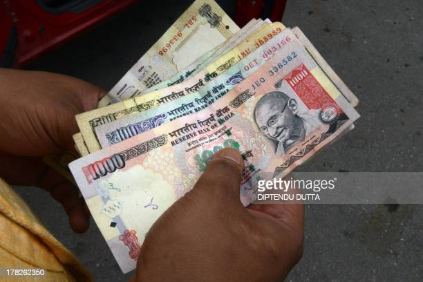An Indian petrol pump employee counts Indian currency in Siliguri on August 28 2013 India's rupee slumped nearly four percent to a fresh record low...