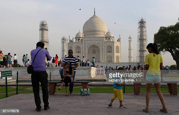 An Indian photographer takes a picture of a couple as they pose in front of the Taj Mahal monument in Agra on April 16 2016 Britain's Prince William...